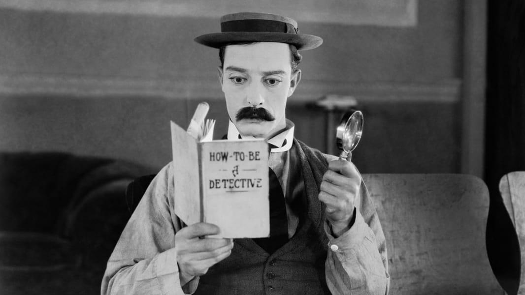 Buster Keaton reading intently in the film 'Sherlock Junior'