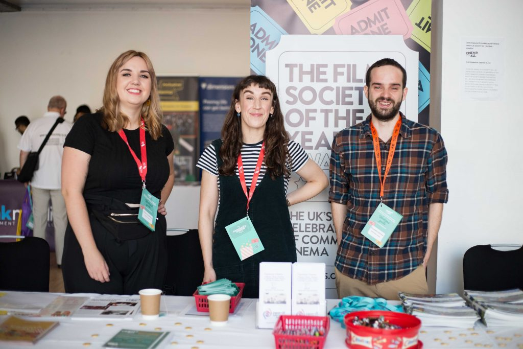 A group of Cinema For All staff stand at a booth decorated with Community Cinema Conference standees and flyers.