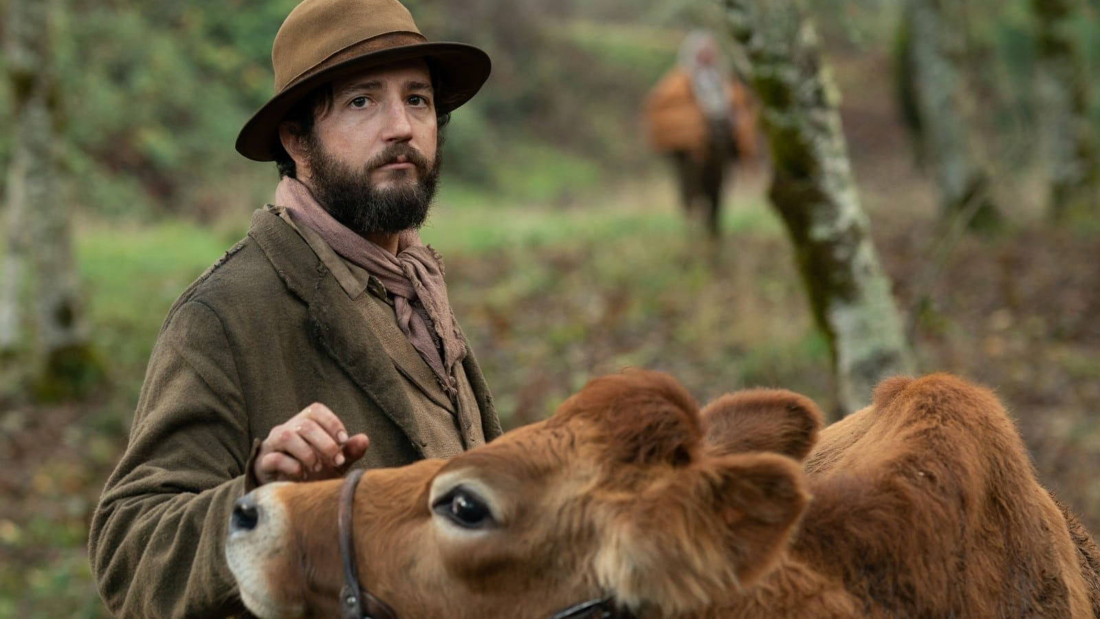 A man stands, looking at the camera, holding a cow. A still from the film First Cow.