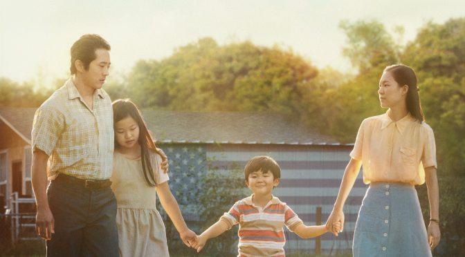 Image of a family, holding hands in the sun. A still from the film Minari.